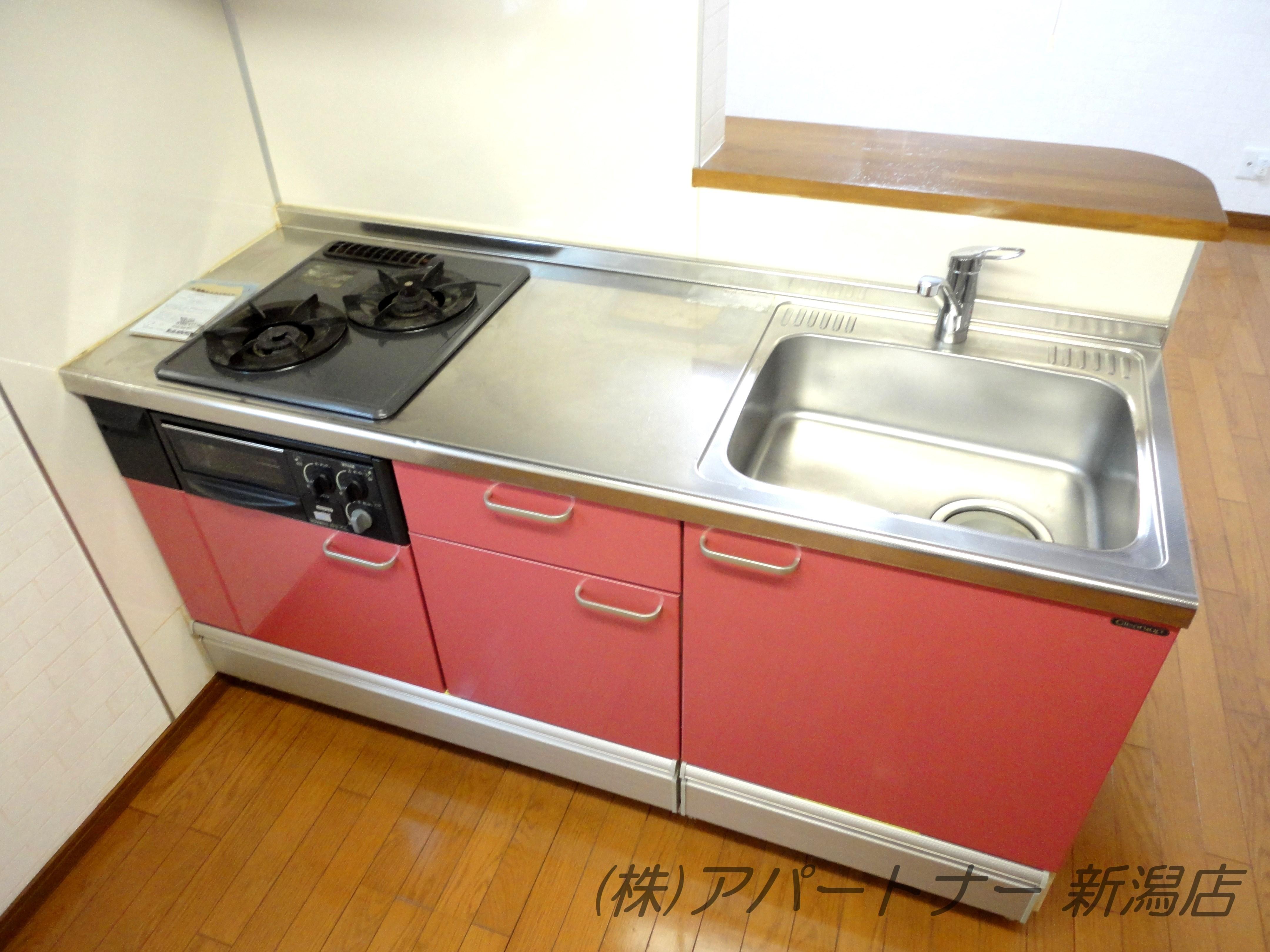 ビルトインガスコンロ(2口)完備のピンク色のかわいいシステムキッチン。