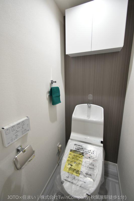 吊戸棚にはトイレットペーパー等を収納できて便利。もちろん温水洗浄機能付です。