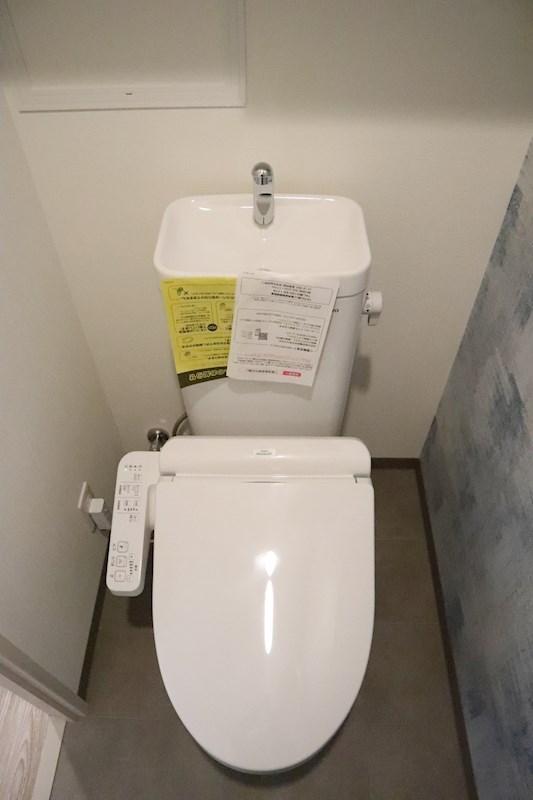温水洗浄便座です。トイレの上には収納棚があり、トイレを清潔に保てます。